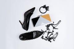 Paare der schwarzen Schuhe verziert mit Metallakzenten, Schmuck mit schwarzer Spitze und Perlen und einer dreifarbigen Kupplung m stockfotos