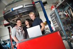 Paare in der Selbstreparaturwerkstatt, die mit Mechaniker steht Lizenzfreie Stockfotos