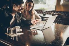 Paare an der Stange unter Verwendung eines Laptops Lizenzfreie Stockbilder