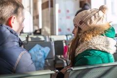 Paare in der warmen Kleidung im Warteraum an der Station Lizenzfreie Stockfotografie