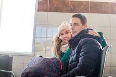 Paare in der warmen Kleidung im Warteraum an der Station Lizenzfreies Stockbild