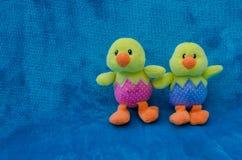 Paare der weichen Spielzeug Ostern-Babyküken auf blauem Hintergrund - Horizont Stockbild