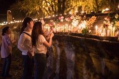 Paare des Buddhisten setzten die Kerzen auf die Wand nach candlelit Prozession bei WatMahaeyong auf Magha Puja Day lizenzfreie stockfotos