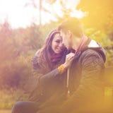 Paare des bunten Herbstwaldes, sitzend auf einer Bank stockbild