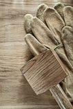 Paare des hölzernen Holzhammers der ledernen Schutzhandschuhe auf hölzernem Brett ' Lizenzfreie Stockbilder