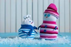 Paare des handgemachten Schneemannes mit gestreiften Strickjacken Stockfoto