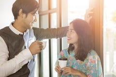 Paare des jüngeren asiatischen Mannes und der Frau mit Kaffeetasse in der Hand t Stockbild