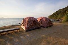 Paare des kampierenden Zeltes im Schrifttyp des Seestrandes mit Morgenleuchte Stockfoto