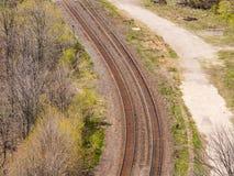 Paare des Kurvens von Bahngleisen nähern sich Wald Stockfoto