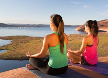 Paare des Mädchen-gehenden Yoga am See Powell Lizenzfreie Stockfotografie