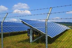 Paare des Sonnenkollektors eingezäunt in einem rostigen Stacheldraht Stockbilder