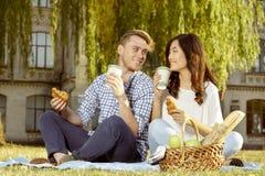 Paare des trinkenden Kaffees des netten Studenten und der essen Hörnchen stockbilder