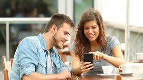 Paare, die über intelligenten Telefoninhalt sprechen stock footage