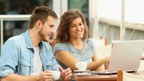 Paare, die über Laptopinhalt in einer Stange sprechen stock video footage