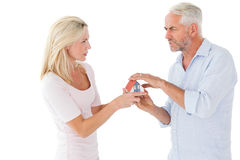 Paare, die über Miniaturmusterhaus kämpfen Stockbild