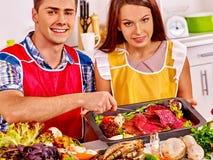 Paare, die Abendessen des rohen Fleisches an der Küche kochen Lizenzfreie Stockfotografie