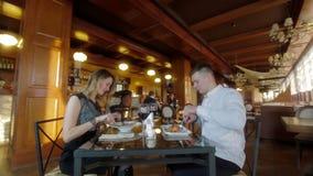 Paare, die Abendessen am Restaurant plaudern und genießen stock footage