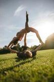 Paare, die acro Yoga auf Gras tun Lizenzfreies Stockfoto