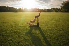 Paare, die acro Yoga im Rasen tun Stockfoto