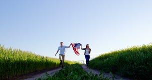 Paare, die amerikanische Flagge und Betrieb auf dem Gebiet halten stock video footage