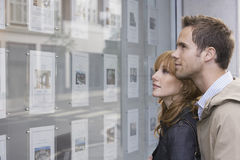 Paare, die Anzeige in Real Estate-Büro betrachten Stockbilder