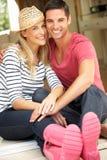 Paare, die außerhalb des Hauses sitzen Stockfoto