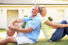 Paare, die außerhalb des Traumhauses sitzen Lizenzfreie Stockfotografie