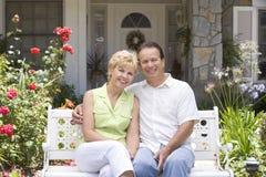 Paare, die auf Bank außerhalb des Hauses sitzen stockfotografie