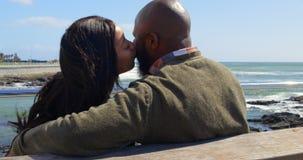 Paare, die auf Bank nahe Geländer an einem sonnigen Tag 4k küssen stock video