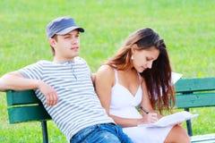 Paare, die auf Bank sitzen Stockfotografie