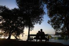 Paare, die auf Bank sitzen Stockbild