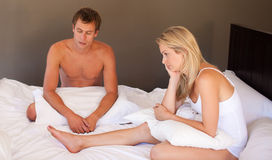 Paare, die auf Bett in der Ruhe sitzen Lizenzfreie Stockfotos
