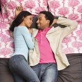 Paare, die auf Bett legen.