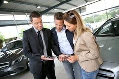 Paare, die auf Broschüre im Autoshop mit Händler überprüfen Lizenzfreie Stockfotos