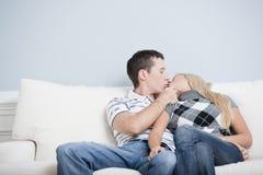 Paare, die auf Couch küssen Lizenzfreie Stockbilder