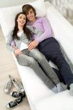 Paare, die auf Couch liegen Lizenzfreies Stockfoto