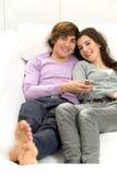 Paare, die auf Couch stillstehen Lizenzfreie Stockbilder