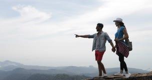 Paare, die auf das Gebirgsschürer-und -frauen-Händchenhalten betrachtet Landschaftsskyline in der Morgen-Touristen-Reise gehen stock video footage