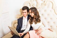 Paare, die auf dem Bett betrachtet Foto sitzen Lizenzfreie Stockfotografie