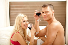 Paare, die auf dem Bett trinken Stockbilder