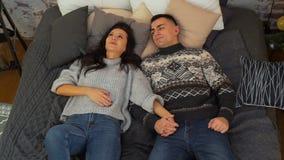 Paare, die auf dem Bett und dem Gespräch liegen stock video footage