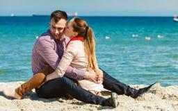 Paare, die auf dem entspannenden und umarmenden Strand sitzen Lizenzfreie Stockfotografie
