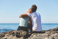 Paare, die auf dem Felsen sich umarmt sitzen lizenzfreie stockfotos