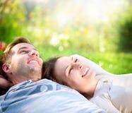 Paare, die auf dem Gras im Freien liegen Stockfotografie