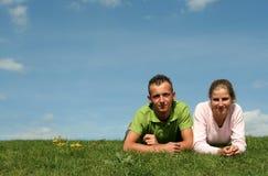 Paare, die auf dem Gras liegen Stockbild