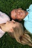 Paare, die auf dem Gras liegen Stockfotos