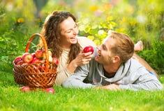 Paare, die auf dem Gras sich entspannen und Äpfel essen Lizenzfreies Stockfoto