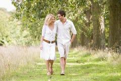 Paare, die auf dem Pfadlächeln gehen Stockfotografie