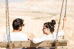 Paare, die auf dem Schwingen sitzen lizenzfreie stockfotos