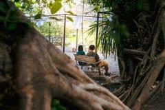 Paare, die auf dem Schwingen sitzen stockbilder